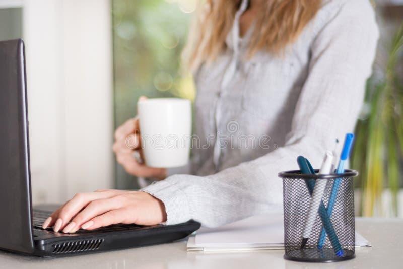 Ung affärskvinna i det moderna kontoret som arbetar på bärbar dator- och innehavkoppen kaffe arkivfoto