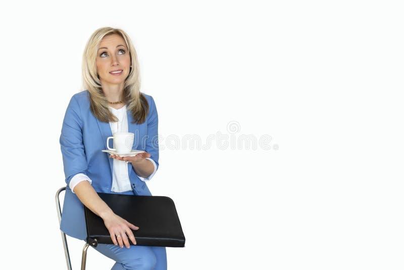 ung affärskvinna i ett omslag med en kontorsmapp och en kopp kaffe, en blond kvinna för affärsstående i en blå dräkt Busine royaltyfri foto