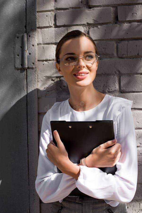 Ung affärskvinna i formella kläder och exponeringsglas som lutar på väggen arkivbild