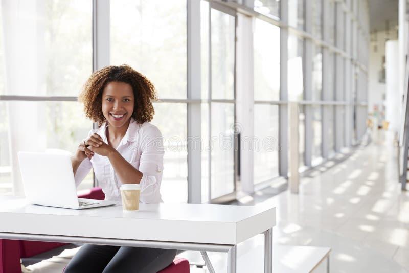 Ung affärskvinna med bärbara datorn på skrivbordet som ser till kameran arkivbild