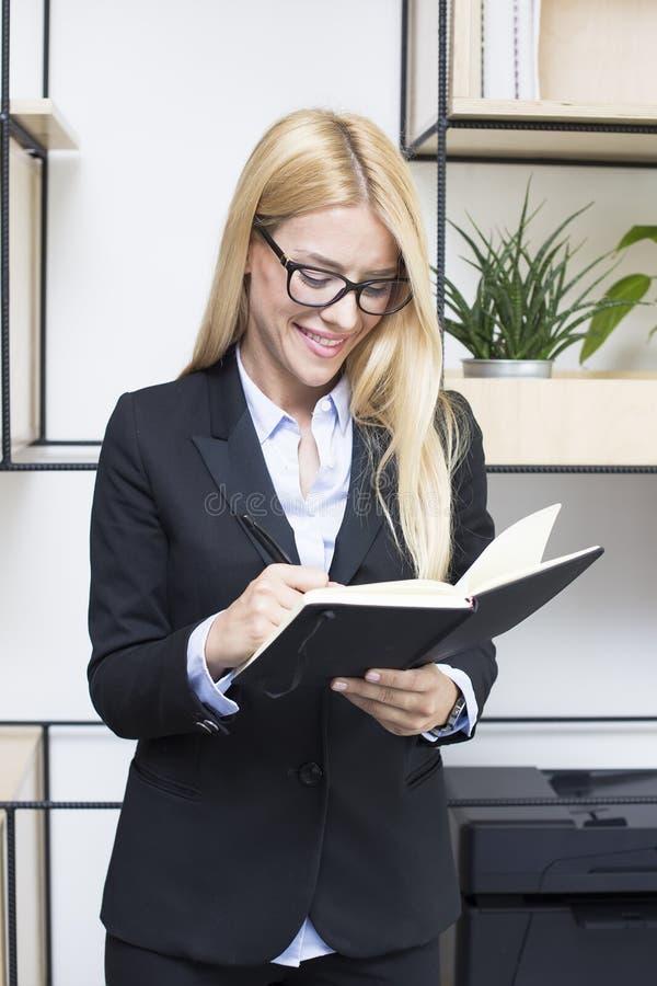 Ung affärskvinna med dagordninganseende i modernt kontor royaltyfri fotografi