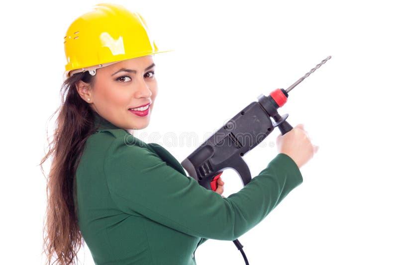 Ung affärskvinna med den hårda hatten som rymmer en drillborr royaltyfri fotografi