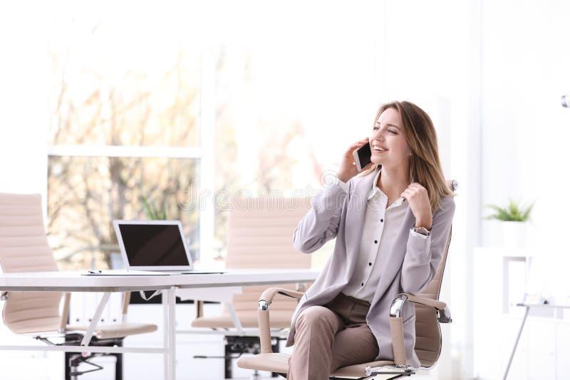 Ung affärskvinna med den smarta telefonen som i regeringsställning sitter stol på arbetsplatsen royaltyfria bilder