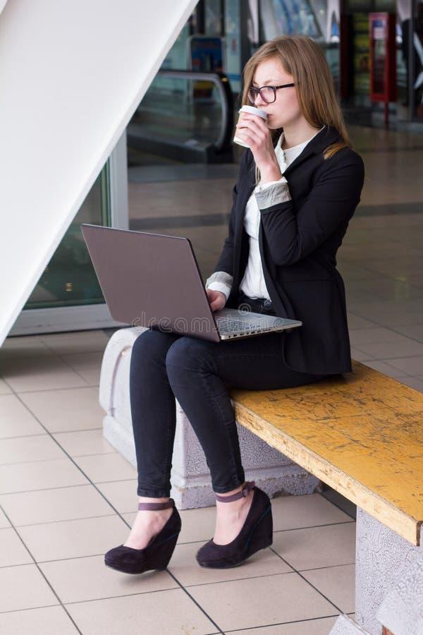 Ung affärskvinna med en bärbar dator som dricker kaffe arkivfoto