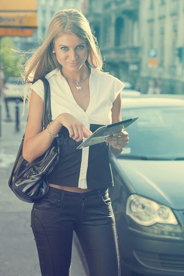 Ung affärskvinna med minnestavladatoren som går på stads- stree royaltyfria bilder