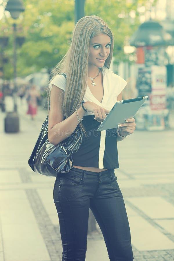 Ung affärskvinna med minnestavladatoren som går på stads- stree royaltyfria foton