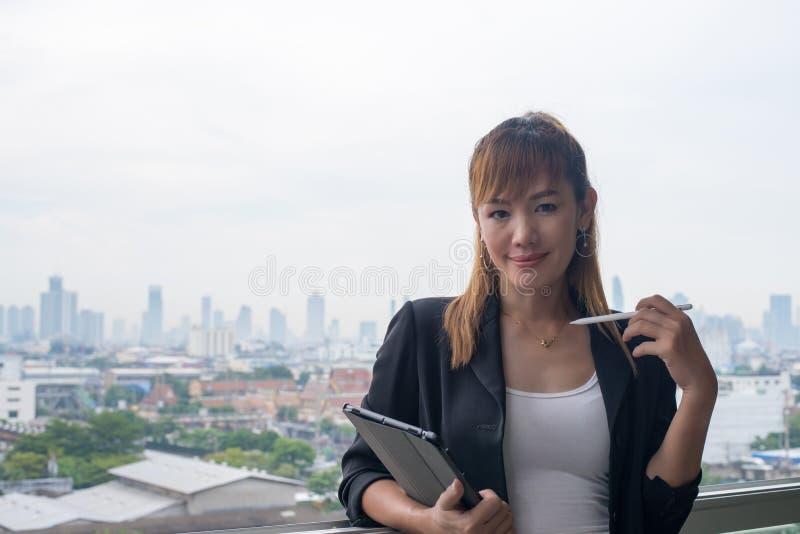 Ung affärskvinna med minnestavlan i kontoret mot panorama- arkivfoton