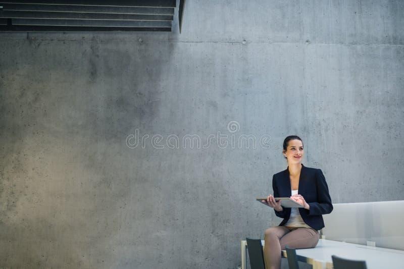 Ung affärskvinna med minnestavlan som i regeringsställning sitter på skrivbordet mot betongväggen royaltyfria bilder