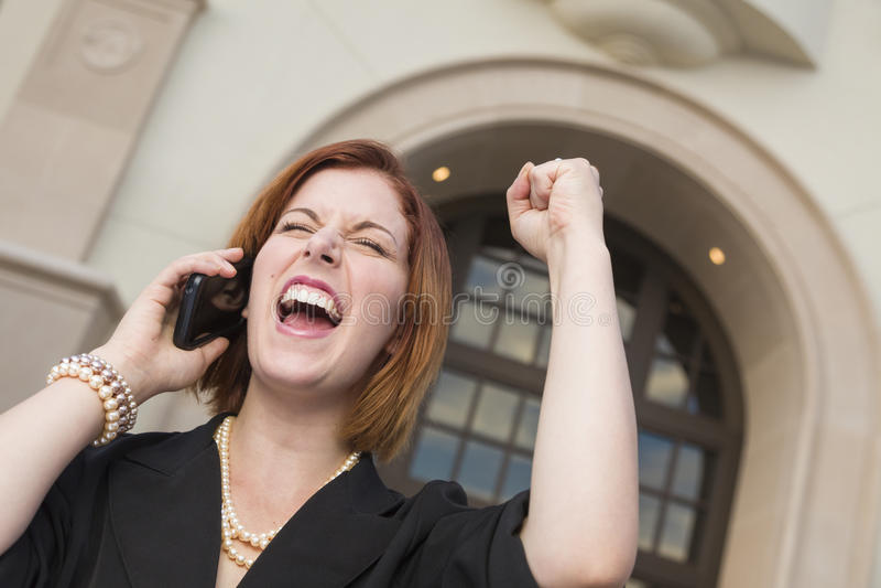 Ung affärskvinna med näven i luft på mobiltelefonen royaltyfria bilder