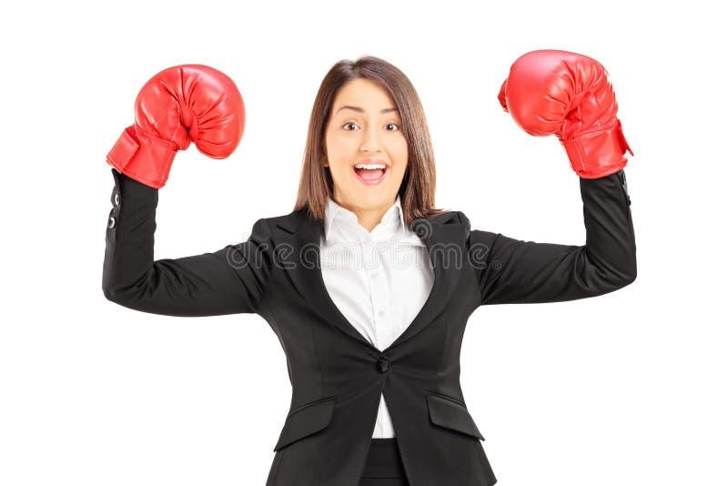 Ung affärskvinna med röda boxninghandskar som gör en gest framgång