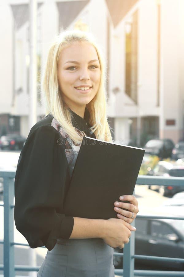 Ung affärskvinna med skrivplattaanseende på balkongen av kontoret royaltyfri bild