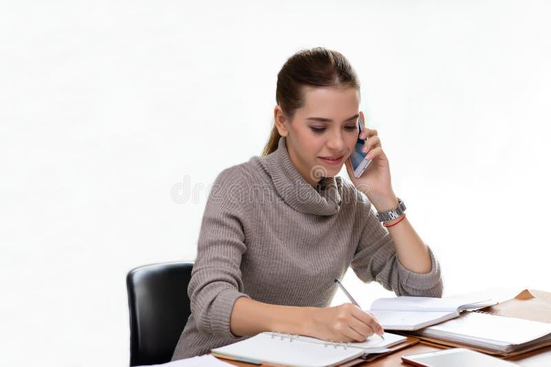 Ung affärskvinna på arbete som talar på telefonen och tar anmärkningar royaltyfria foton