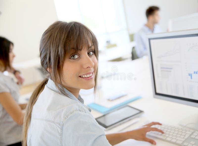 Ung affärskvinna på datoren, kollegor i bakgrund arkivbild