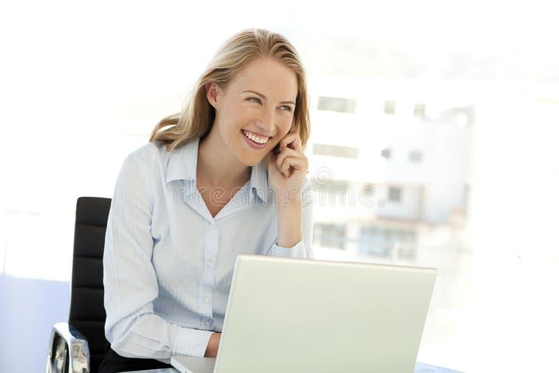 Ung affärskvinna på telefonen på arbetsplatsen royaltyfri bild