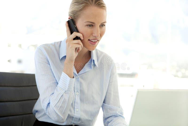 Ung affärskvinna på telefonen på arbetsplatsen royaltyfria foton