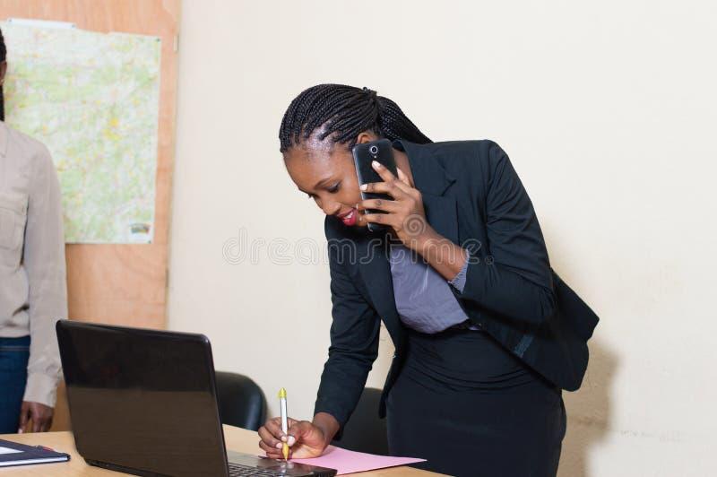 Ung affärskvinna på telefonen som tar anmärkningar royaltyfri fotografi