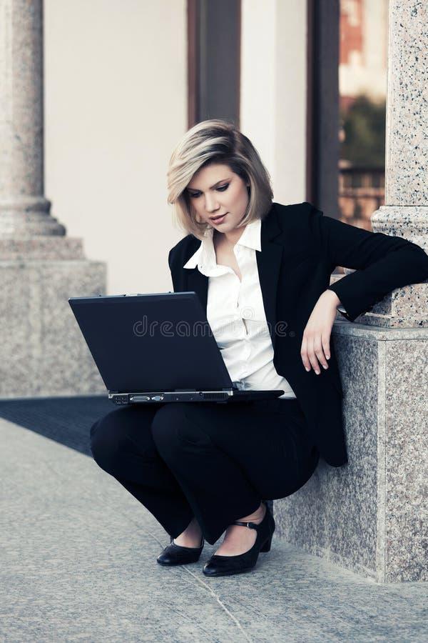 Ung affärskvinna som använder bärbara datorn på kontorsbyggnad royaltyfri bild