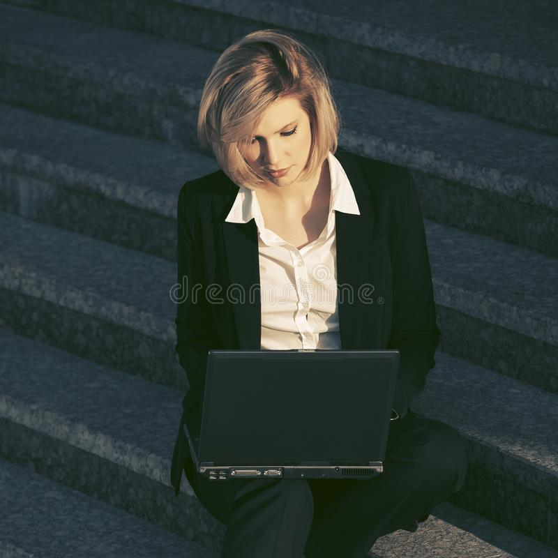 Ung affärskvinna som använder bärbara datorn på momenten fotografering för bildbyråer