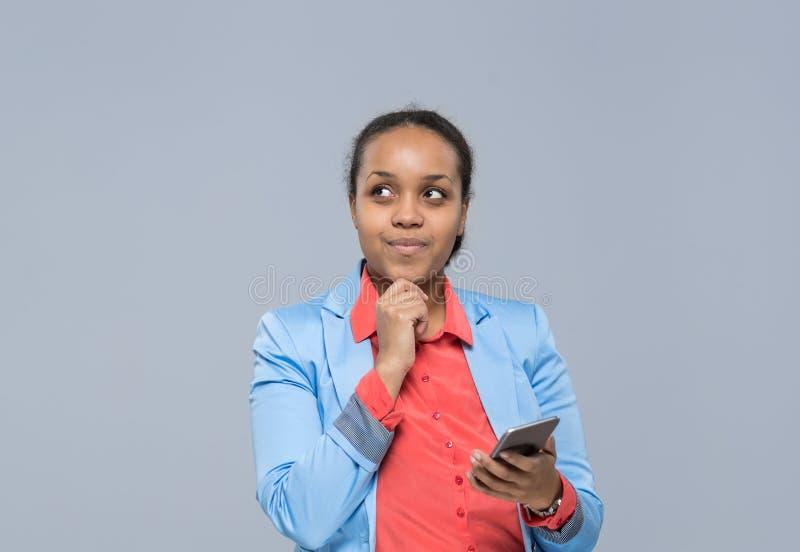 Ung affärskvinna som använder flickan för afrikansk amerikan för cellSmart telefon som ser för att kopiera utrymmeaffärskvinnan royaltyfria foton