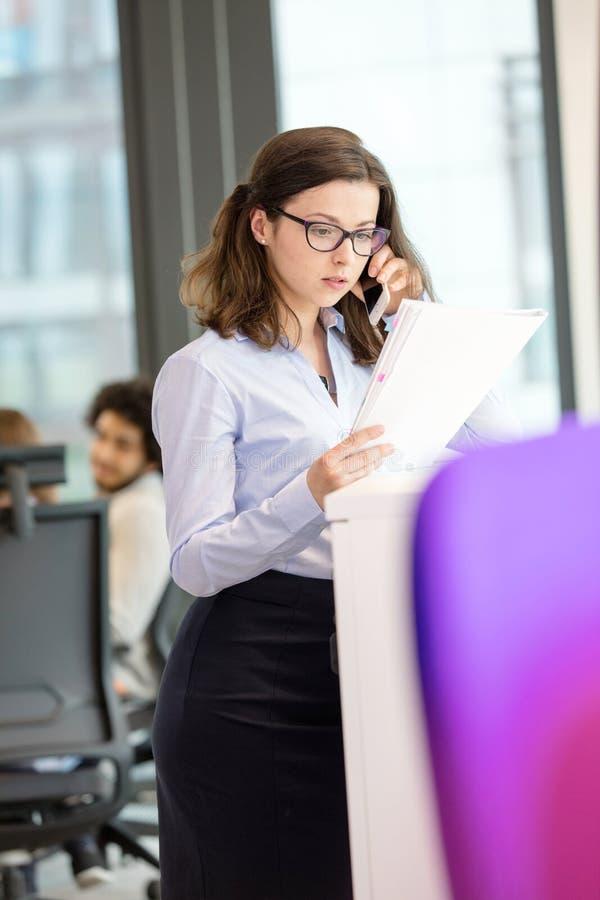 Download Ung Affärskvinna Som Använder Mobiltelefonen Medan Läsebok I Regeringsställning Arkivfoto - Bild av fotografi, affär: 78728560