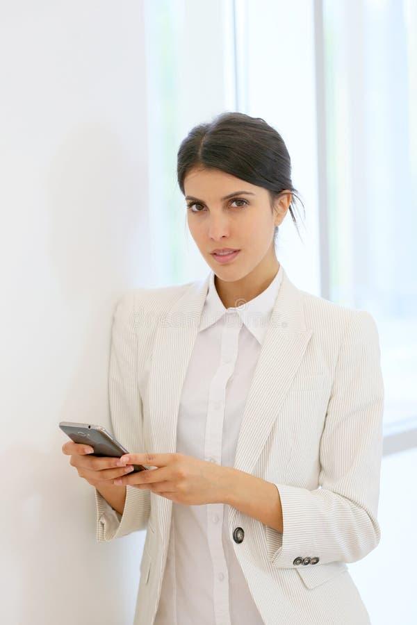 Ung affärskvinna som använder smartphonen royaltyfri bild