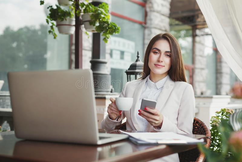 Ung affärskvinna som använder smartphonen och dricker utomhus kaffe royaltyfria foton