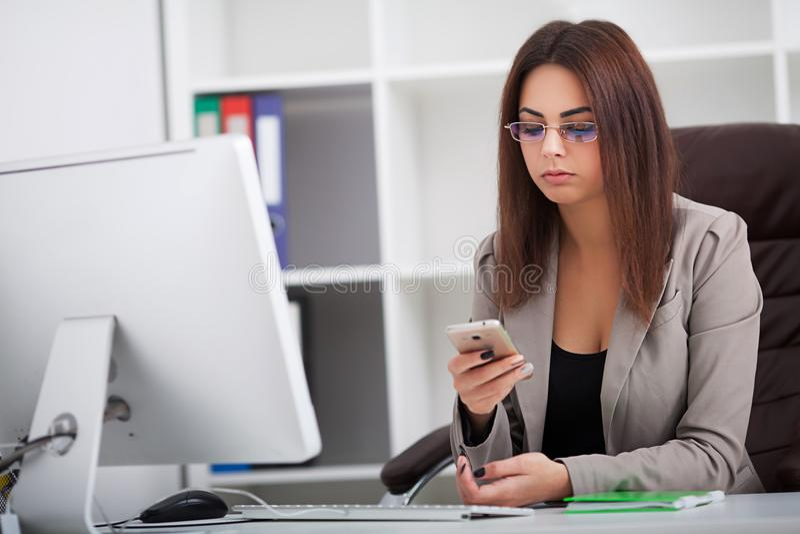 Ung affärskvinna som arbetar på bärbara datorn och talar på mobil pho royaltyfri foto