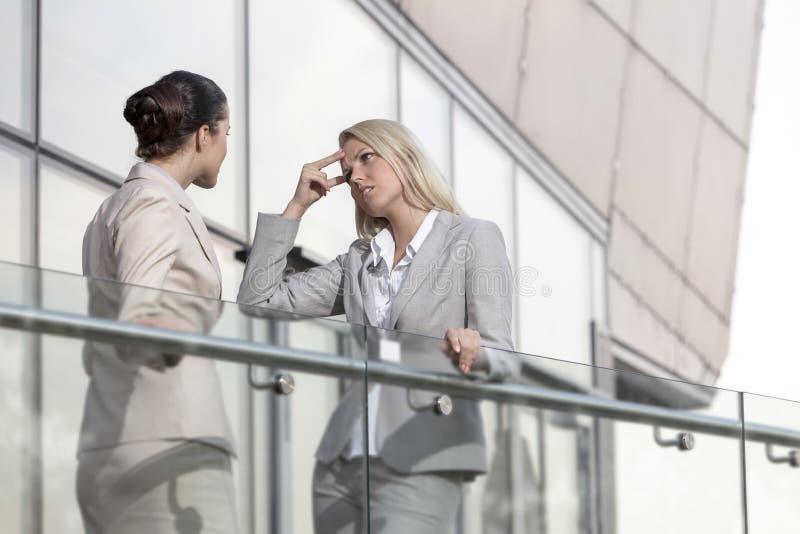 Ung affärskvinna som argumenterar med den kvinnliga kollegan på kontorsräcket fotografering för bildbyråer