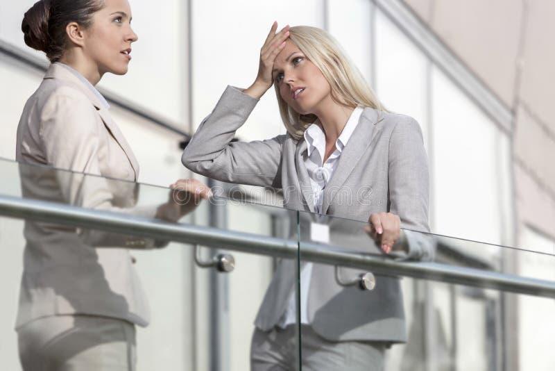 Ung affärskvinna som argumenterar med den kvinnliga kollegan på kontorsräcket arkivbilder