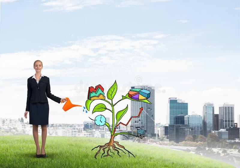 Ung affärskvinna som bevattnar utomhus dragit tillväxtbegrepp med canen arkivbild