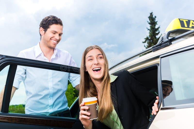 Ung affärskvinna som får ut ur taxien