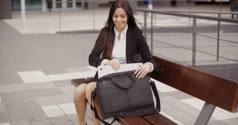 Ung affärskvinna som förlägger hennes bärbar dator i en påse arkivbild