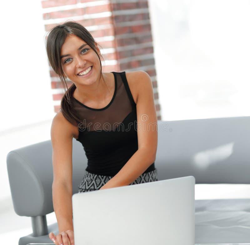 Ung affärskvinna som framme sitter av en öppen bärbar dator arkivfoton