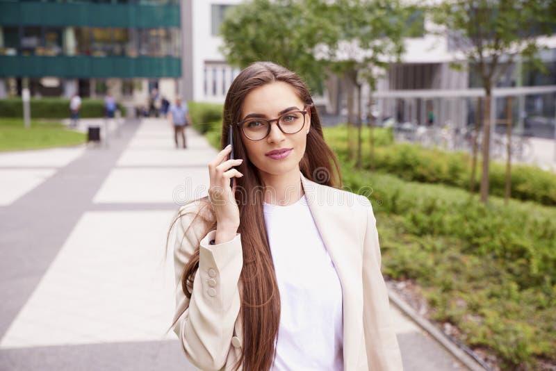 Ung affärskvinna som gör en appell, medan gå på gatan royaltyfria bilder