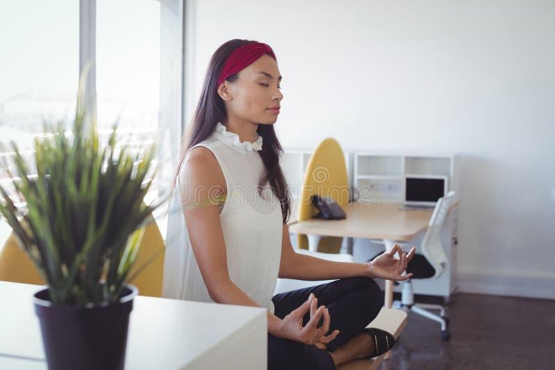 Ung affärskvinna som gör yoga på kontoret royaltyfri bild