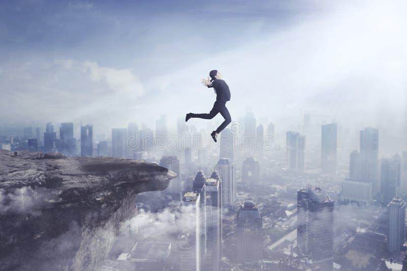 Ung affärskvinna som hoppar av en klippa arkivfoton
