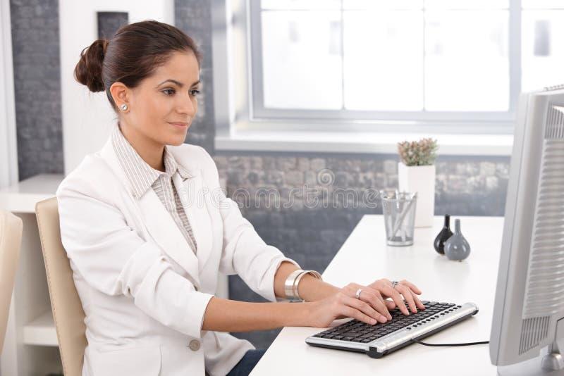 Ung affärskvinna som i regeringsställning fungerar arkivfoto