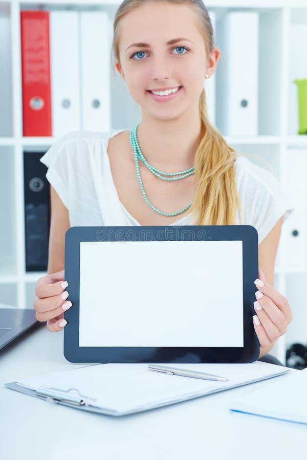 Ung affärskvinna som i regeringsställning visar den tomma skärmen av minnestavlaPC:n arkivfoton