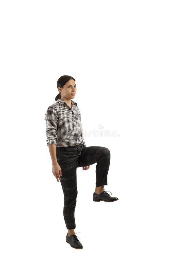 Ung affärskvinna som isoleras på vit bakgrund som gör övningar arkivfoton