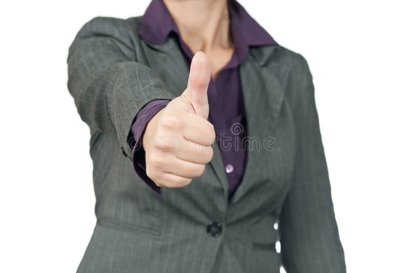Ung affärskvinna som lyfter handen och visar teckenok. arkivfoto