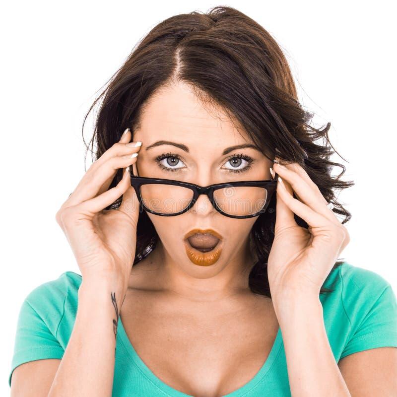 Ung affärskvinna som rymmer exponeringsglas som ser chockade royaltyfri fotografi