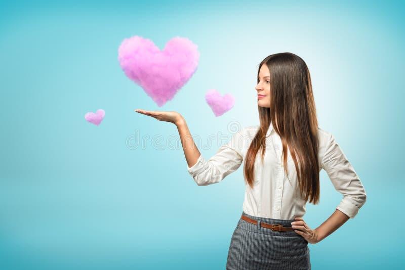 Ung affärskvinna som rymmer rosa molnhjärta på hennes hand på blå bakgrund royaltyfri bild
