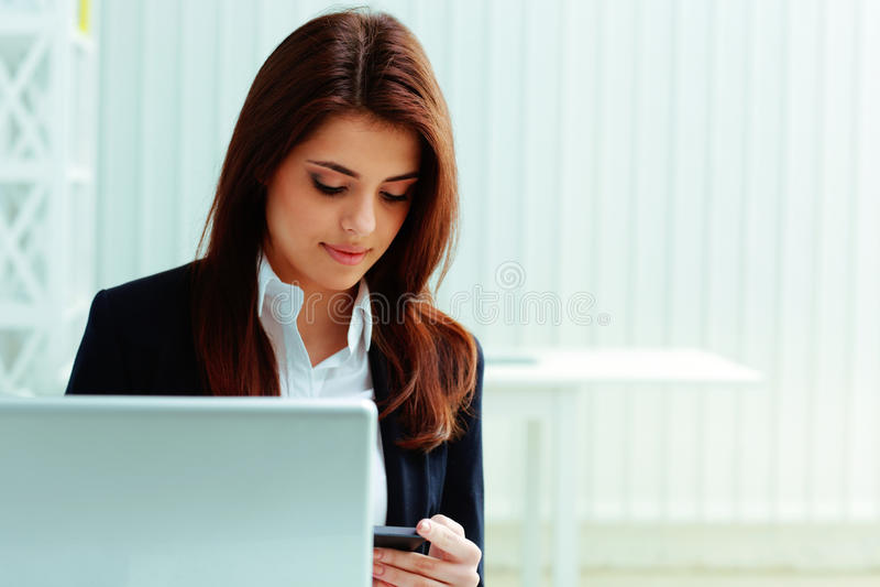 Ung affärskvinna som ser smartphonen royaltyfria bilder
