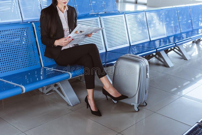 ung affärskvinna som sitter på avvikelsevardagsrummet i flygplats och royaltyfri foto