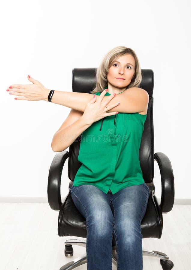 Ung affärskvinna som sitter på stol som gör konditionövning på arbetsplatsen royaltyfria foton