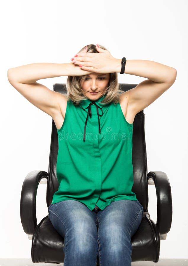Ung affärskvinna som sitter på stol som gör konditionövning på arbetsplatsen arkivfoton