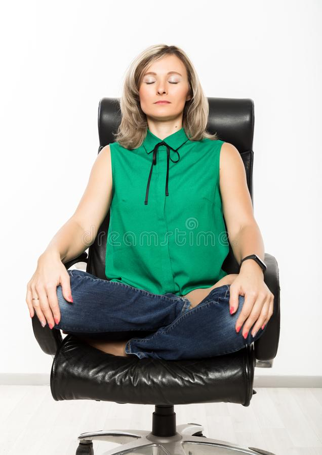 Ung affärskvinna som sitter på stol som gör konditionövning på arbetsplatsen arkivbild