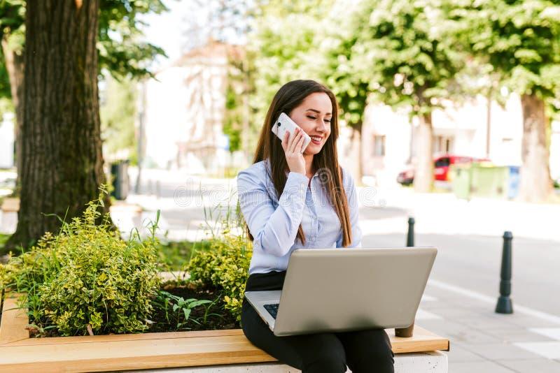 Ung affärskvinna som sitter utomhus- samtal på telefonen, medan arbeta på bärbara datorn royaltyfri fotografi