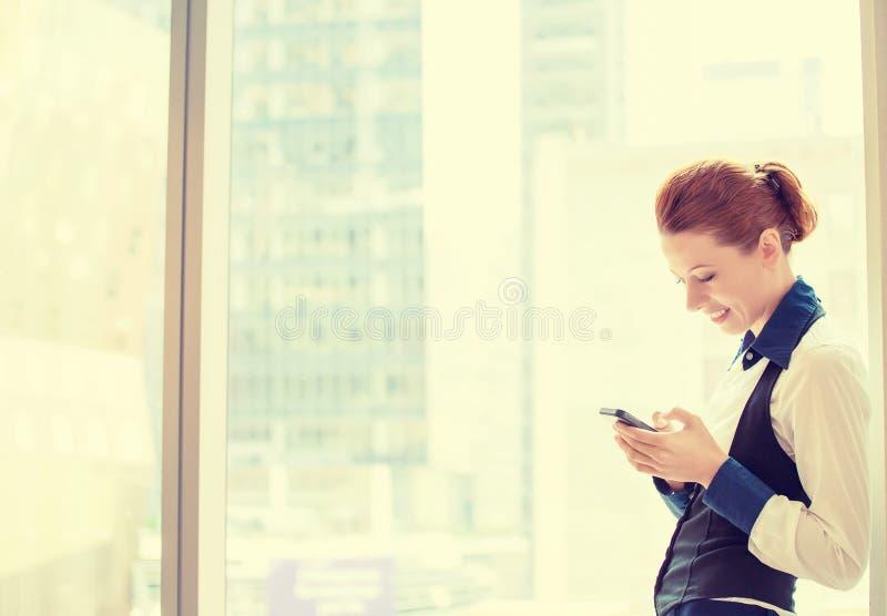 Ung affärskvinna som smsar på hennes smarta telefon arkivfoto