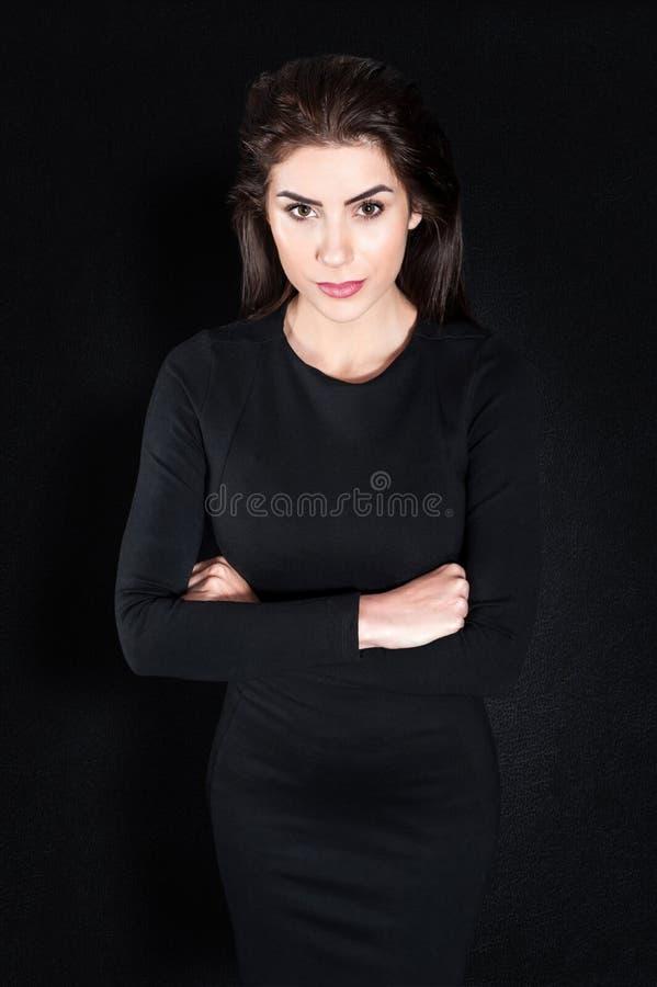 Ung affärskvinna som står allvarlig mot svart bakgrund royaltyfri fotografi